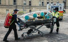 Парамедици, транспортиращи изолиран пациент